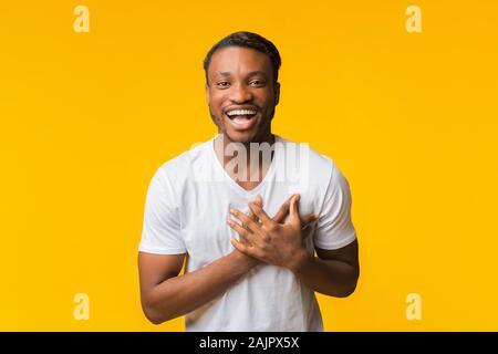 African American Man positive tous les coeur poitrine toucher à la caméra à l'article sur fond jaune. Studio Shot
