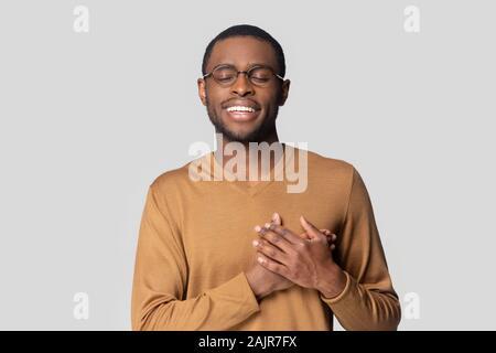 Guy africaine La main reste toujours sur la poitrine montrant gratitude studio shot