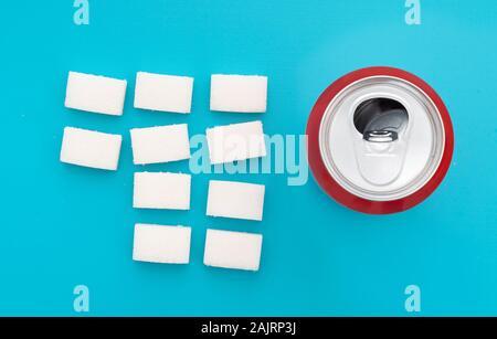 Concept d'aliments malsains - le sucre dans les boissons gazeuses. Le sucre en cubes et fizzy boisson coca peut. Mise à plat, vue de dessus.