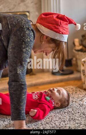 Un petit garçon, premier Noël (bébé de sexe masculin, homme, enfant) - Rire de sa mère (Maman, Maman) wearing a Santa Hat sur un tapis au coin du feu Banque D'Images