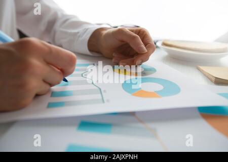 Mains d'analyste financier travailler avec rapport graphique. Statistiques, comptabilité personne d'affaires.