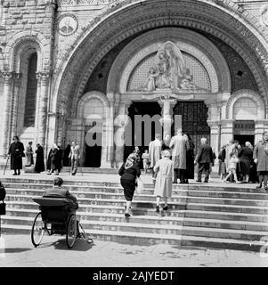 Années 1950, visiteurs à l'entrée de la Basilique Rosaire, Lourdes, France, une église catholique à la 'Sanctuaire de la Vierge De Lourdes' ou au domaine, une région de terre entourant le sanctuaire catholique (Grotto). Un lieu de pèlerinage pour beaucoup de la foi chrétienne, en particulier les malades et les infirmes, comme on peut le voir sur la photo par un homme dans un transport invalide de l'époque par les marches de l'église.