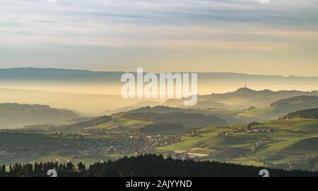 Village couvert dans le brouillard pendant le coucher du soleil avec une lumière chaude et une tour de diffusion à l'arrière-plan Banque D'Images