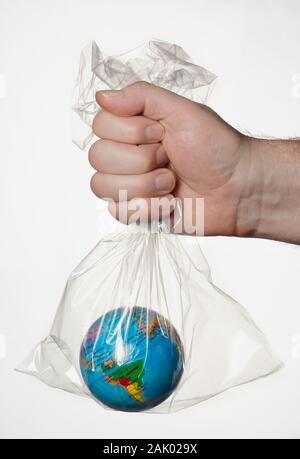 Une main humaine tenant la terre dans un sac en plastique transparent.