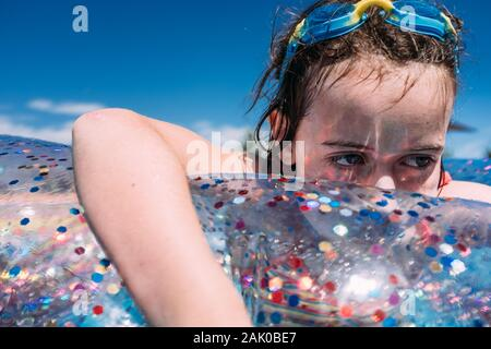 gros plan d'une fille triste qui flotte dans la piscine avec des lunettes sur la tête