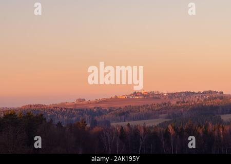 coucher de soleil sur le paysage rural avec village - dans la forêt de premier plan, à l'horizon sur l'église de colline et plusieurs bâtiments, ciel orange Banque D'Images