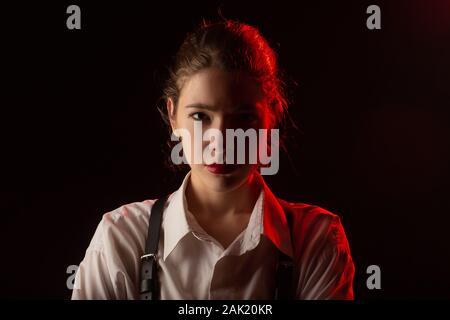 Jeune femme sérieuse dans le noir à la caméra à image tonique Banque D'Images