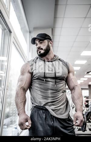 Beau jeune homme sportif sport à cap et hoodie près de fenêtre dans fitness club de sport au cours d'entraînement de formation Banque D'Images