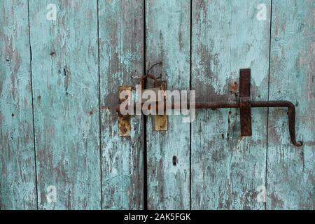 Verrou porte rouillée et d'un cadenas de verrouillage coulissant sur old weathered barrière en bois avec peinture bleue écaillée. Banque D'Images