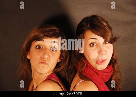 Deux jeunes femmes qui font des gestes, regardant l'appareil photo. Banque D'Images
