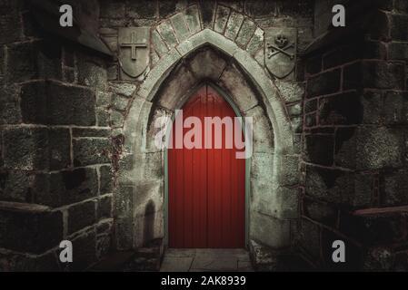 Porte en bois rouge pointu effrayant dans un vieux mur de pierre humide et bâtiment avec cross, du crâne et des os des deux côtés. Mystère, la mort et la notion de danger.