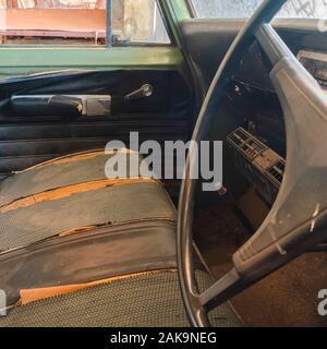 Old vintage carré de voiture avec le volant et l'intérieur sale Banque D'Images