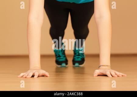 Stock photo d'une jeune femme faisant push-ups à la maison