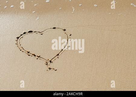 Forme de coeur dessiné dans le sable à la plage Banque D'Images