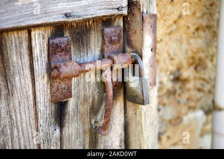Image d'un boulon rouillé boor coulissante avec cadenas sur vieil porte. Banque D'Images