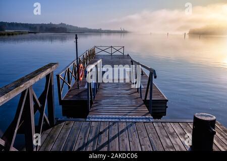 Belle scène tranquille d'une jetée dans la mer de brouillard et le ciel bleu au-dessus.