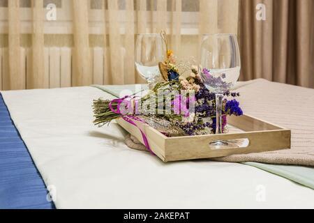 Décoration de la vie encore deux verres de vin vide, un home-made rag angel toy et bouquet de fleurs séchées. Banque D'Images