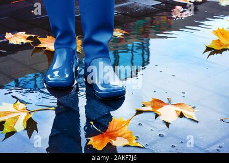Méconnaissable femme portant des bottes de pluie bleu debout en flaque sur automne pluvieux jour.