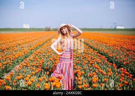 Paysage magique avec de beaux longs cheveux rouges jeune femme portant sur robe rayée et chapeau de paille article coloré de fleurs sur champ de tulipes en Hollande.
