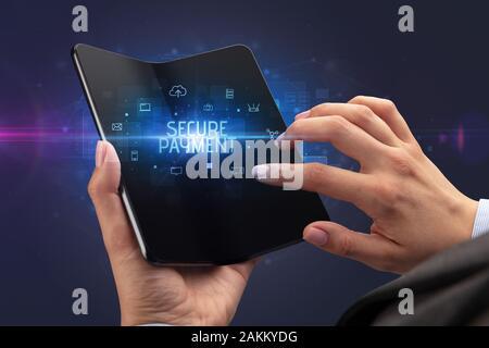 Businessman holding a smartphone pliable avec paiement sécurisé inscription, cyber security concept