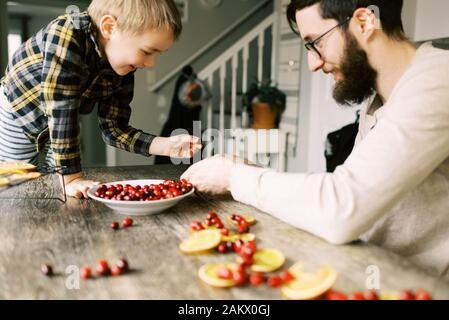 Père et fils qui font des guirlandes d'orange et de canneberges pour Noël. Banque D'Images
