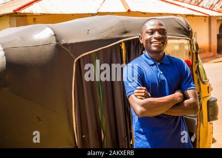 un jeune homme africain qui conduit un taxi en pousse-pousse compte sur son argent souriant