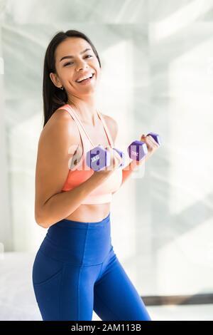 Jeune femme est l'entraînement avec haltères à la maison. La condition physique, entraînement, vie saine et l'alimentation de concept.