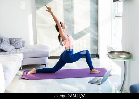Young woman doing yoga exercice et regarder l'exercice sur ordinateur portable à la maison Banque D'Images