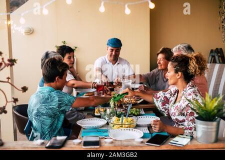 Famille mixte générations ayant déjeuner ensemble à la maison ou au restaurant concept - jeunes adultes et hommes et femmes âgés avec de la nourriture sur la table - pas de techon Banque D'Images