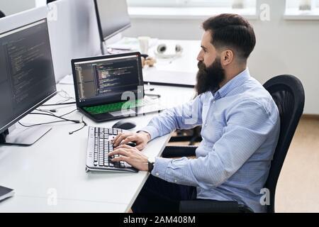 Développeur de programmeurs informatiques travaillant dans le bureau INFORMATIQUE, assis au bureau et codage, travaillant sur un projet dans une société de développement de logiciels ou de démarrage. Banque D'Images