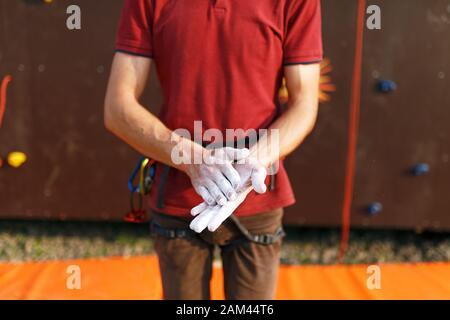 Gros plan sur le revêtement de l'homme grimpant les mains en poudre de craie de magnésium et se préparant à monter l'entraînement extérieur de mur de roche d'entraînement. Banque D'Images