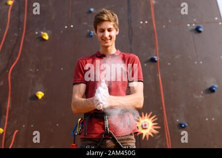 L'homme grimpeur endure les mains dans la craie de poudre de magnésium et se prépare à monter la paroi rocheuse d'entraînement en plein air. Poudre dans l'air après avoir claqué les mains Banque D'Images