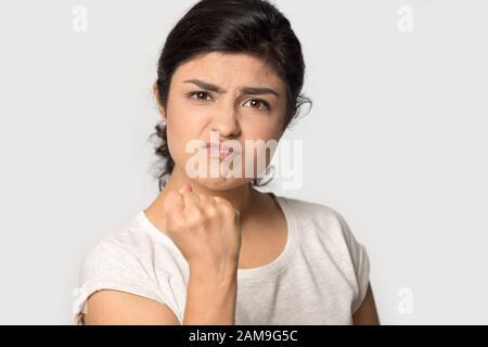 Une jeune femme indienne en colère agressive qui s'est envenchée de poing. Banque D'Images