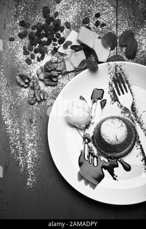 Gâteau de lave fondu français avec silhouette de fourche sur la plaque. Concept de pâtisserie. Fondant au chocolat avec crème glacée et sauce au chocolat sur fond gris. Dessert servi avec des fruits secs dans un café ou une boulangerie. Banque D'Images