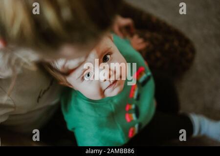 Jeune enfant assis sur les genoux Banque D'Images