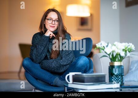 Portrait photo de jeune femme souriante rêvant tout en se reposant sur une chaise à la maison. Banque D'Images