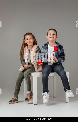 fille et garçon souriants et stylés avec des coeurs rouges sur le bâton dans des vêtements tendance qui se sitting ensemble au studio. concept de mode pour enfants. St Banque D'Images