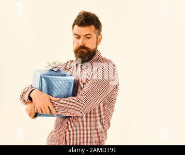 Guy in plaid chemise tasses présent boîte. Macho avec cadeau bleu enveloppé et noeud blanc. Homme avec barbe et visage réfléchi isolé sur fond blanc. Concept de cadeau surprise et de vacances. Banque D'Images