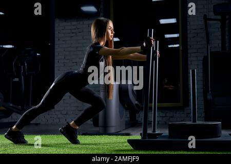 Vue latérale de la jeune femme en tenue de sport noire debout mobile avec poids dans la salle de sport. Athlète féminin fort et attrayant avec de longs équipements de poussée de cheveux. Concept de culturisme, entraînement. Banque D'Images