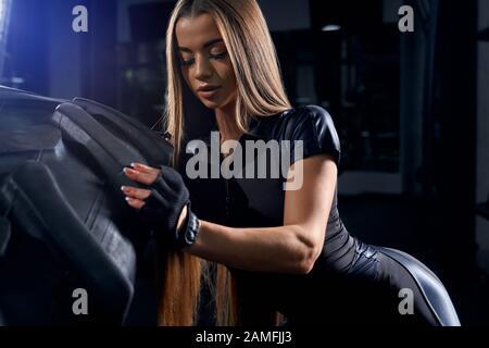 Gros plan de la jeune femme dans les vêtements de sport noirs déplaçant le pneu géant dans la salle de sport. Athlète féminin fort et séduisant avec de longs cheveux poussant la grande roue. Concept de culturisme, entraînement. Banque D'Images