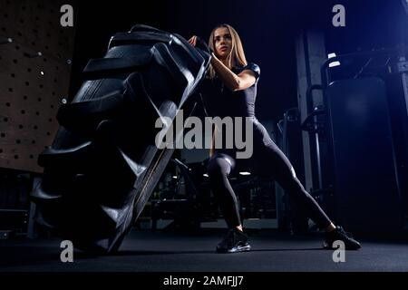 Vue avant de la jeune femme en tenue de sport noire déplaçant le pneu géant dans la salle de sport. Athlète féminin fort et séduisant avec de longs cheveux poussant la grande roue. Concept de culturisme, entraînement. Banque D'Images