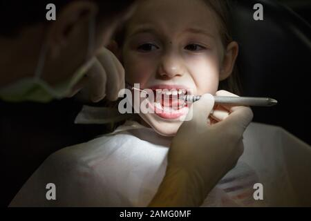 Peur petite fille à l'office, les dentistes dans la douleur lors d'un examen de santé. Les soins dentaires pédiatriques et la peur du dentiste concept.