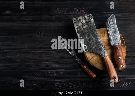 Ancien couteau à viande de boucherie, cale et fourchette sur fond noir Banque D'Images