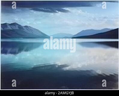 Lac McDonald et montagnes environnantes en soirée, le plus grand lac du parc national des Glaciers, Montana, 1933. Image Reproduite Avec L'Aimable Autorisation Des Archives Nationales. Remarque : l'image a été colorisée numériquement à l'aide d'un processus moderne. Les couleurs peuvent ne pas être précises sur une période donnée. () Banque D'Images