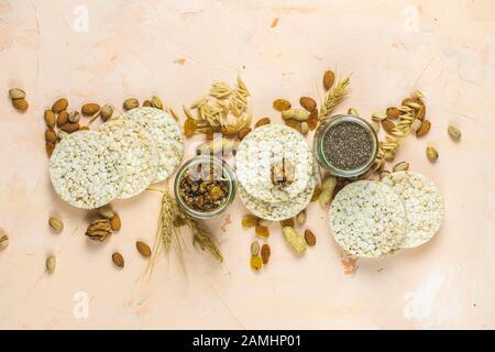 Gâteaux de riz américains à la bouffée. En-cas sains avec oreilles de blé sur surface en béton rose clair, vue de dessus, plat, espace de copie pour vous texte. Banque D'Images
