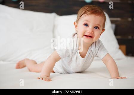 Portrait de bébé rampant sur le lit Banque D'Images