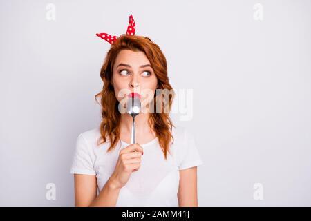 Portrait de l'étonnement des girl lick spoon tenir main copyspace impressionné avec yummy seigneur porter élégant T-shirt isolated over white background couleur Banque D'Images