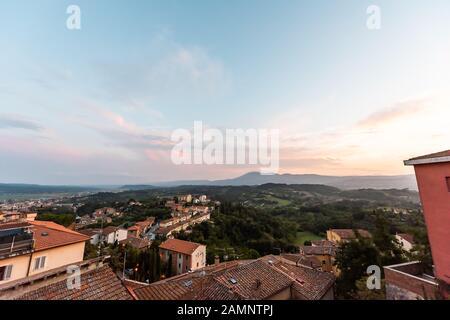 Chiusi, Italie petit village de ville de Toscane au coucher du soleil soir avec des maisons sur le toit sur les collines vallonnées de la campagne de montagne et paysage urbain coloré avec rose Banque D'Images