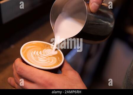 Gros plan sur un barista qui ajoute du lait mousse à un café. Banque D'Images