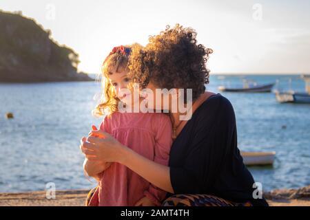 Mère embrassant sa fille sur la plage, Armacao dos Buzios, Rio de Janeiro, Brésil